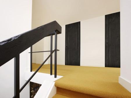 SChwarze Tür, weiße Wand, gelber Boden.